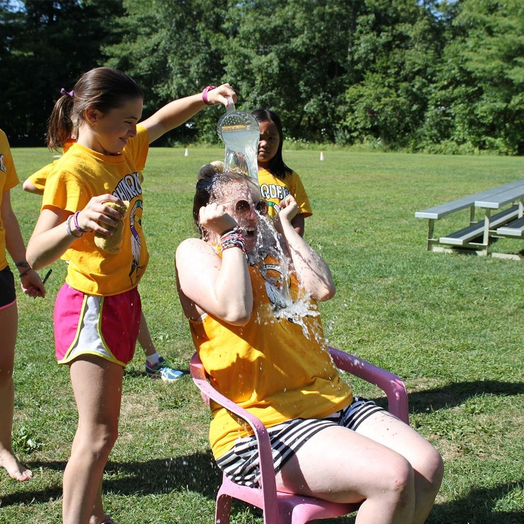 Camp Counselor having water thrown over her head by a camper